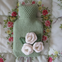 Hand knitted green hot water bottle cover with roses