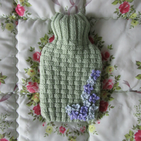 Hand knitted basket weave hot water bottle cover with ditsy flowers
