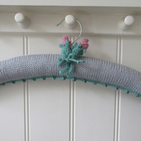 Hand knitted padded silver coat hanger with rose buds