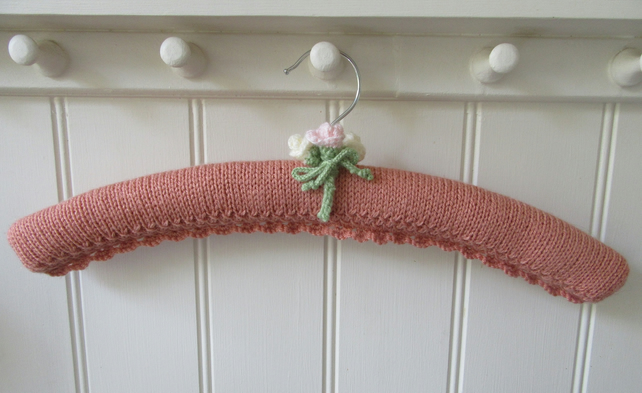 Knitted padded peach coloured coat hanger with rose buds