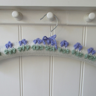 Hand knitted cream coat hanger with lavender bobble bud flowers