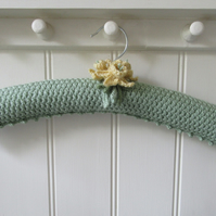 Hand knitted green coat hanger with daffodils