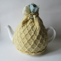 Hand knitted pale yellow tea pot cosie with crocus flowers