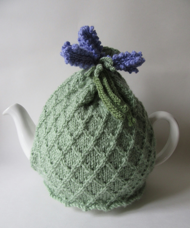 Knitted pastel green tea pot cosie with lavender flowers