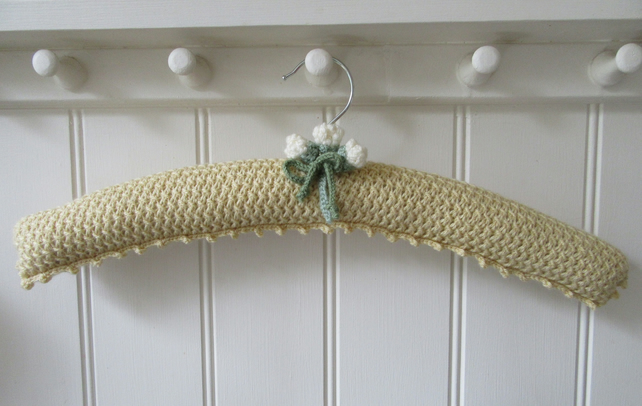 Hand knitted primrose yellow coat hanger with rose buds