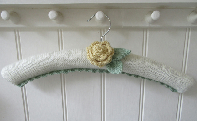 Hand knitted padded coat hanger with ranunculus flower