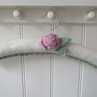 Hand knitted padded coat hanger with a ranunculus flower
