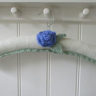 Hand knitted padded cream coat hanger with a ranunculus