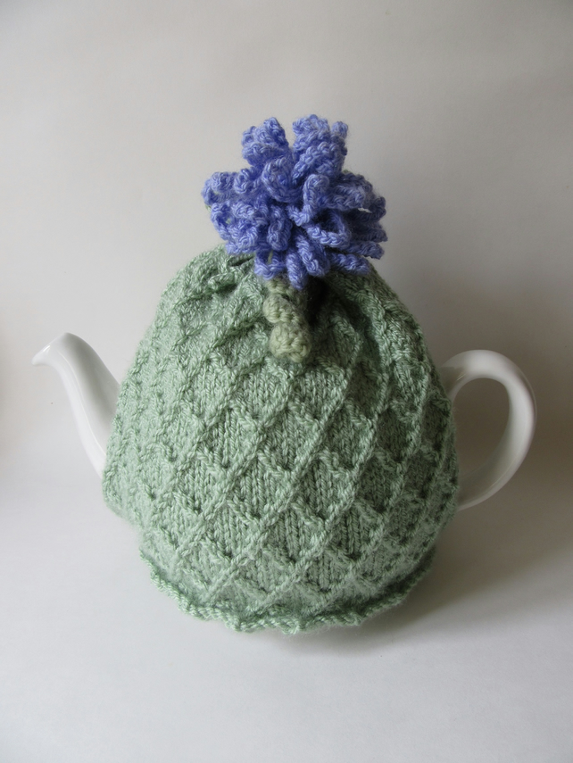 Knitted pastel green trellis tea cosie with allium flower