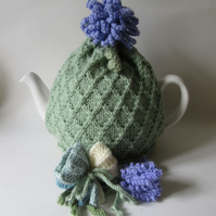 Hand knitted pastel green tea cosie with crocus, allium and lavender flowers