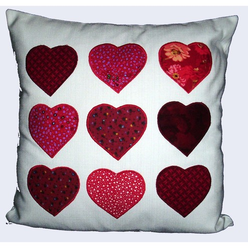 Applique cushion with red hearts