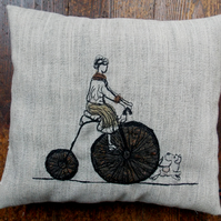 Sybil tries out the old penny-farthing - free motion embroidered cushion.