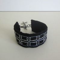 Black cuff bracelet hand embroidered with silver dragonfly