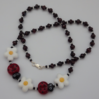 Lampwork glass ladybird and flower bead necklace with faceted garnet beads