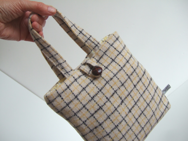 A little woollen bucket bag made from cream and black checked wool.
