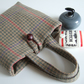 A little woollen bucket bag made from brown and green checked wool.