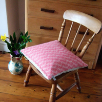 Woollen cushion in pink herringbone tweed with feather pad.