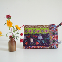 Make up or toiletries bag made from a print with a Folk Art style.