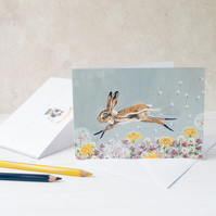 Hare leaping through wild flower meadow greeting note card. A6