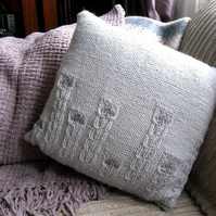 Hand knitted cushion with  rows of cable flowers