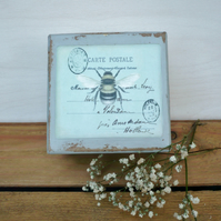 A gift box with a decoupaged bee