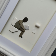 Humorous Pebble Art Picture, Man Sitting on Toilet Reading a Newspaper