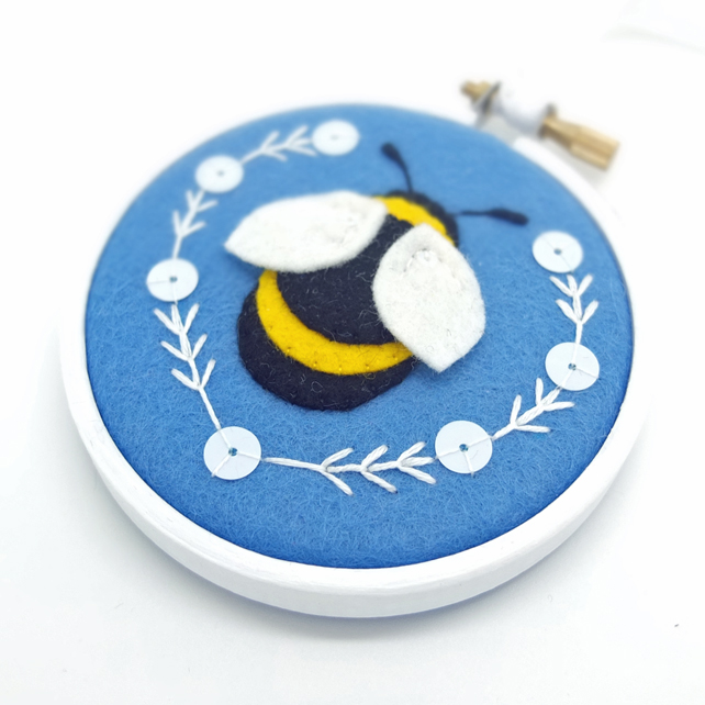 A beautiful embroidery hoop with a bumble bee on a blue background with white embroidered details. It looks soft, puffy and cute.