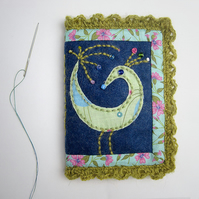 Needle case with appliquéd bird and crochet trim
