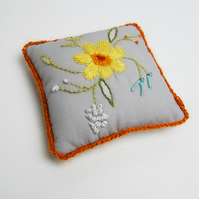 Grey pincushion with hand embroidered spring flowers and orange crochet trim