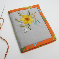 Grey needle case with hand embroidered spring flowers and orange trim