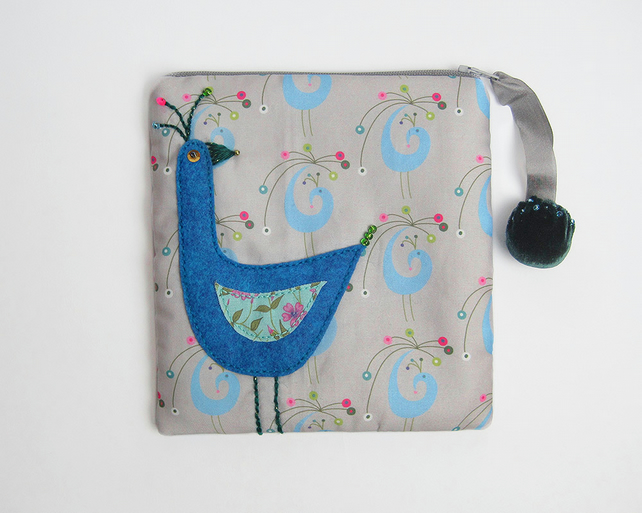 Make up bag with appliquéd bird on peacock printed cotton