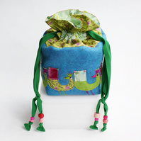 Turquoise wool felt drawstring bag with hand stitched peacocks all around