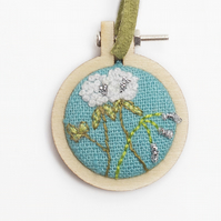 Mini hoop embroidery with hand stitched clover and bluebell on turquoise linen