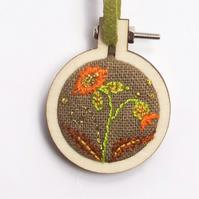 Mini hoop embroidery with hand stitched flowers on brown linen