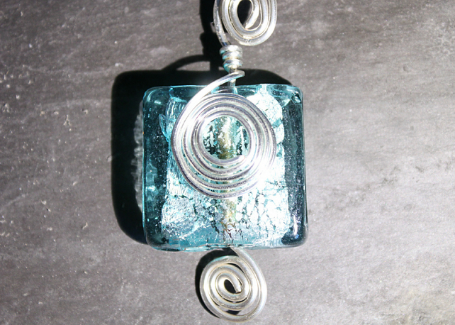 Square light blue foiled glass bead wrapped in spirals of silver wire pendant