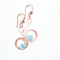 Pale blue faceted glass bead and copper swan spiral dangle earrings