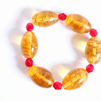 Yellow lampwork bead and red faceted bead elasticated stacking bracelet