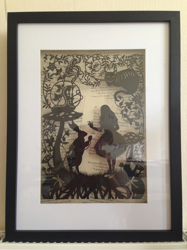 Large paper cut Alice In Wonderland. Floating over vintage book pages