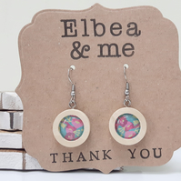 Handmade floral earrings in a natural wood frame.