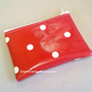 red coin purse with white spots, water resistant, zip