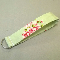 Ladies wrist key ring in green oilcloth with pink flowers