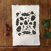 Nature lino print with acorns, berries, and leaves.