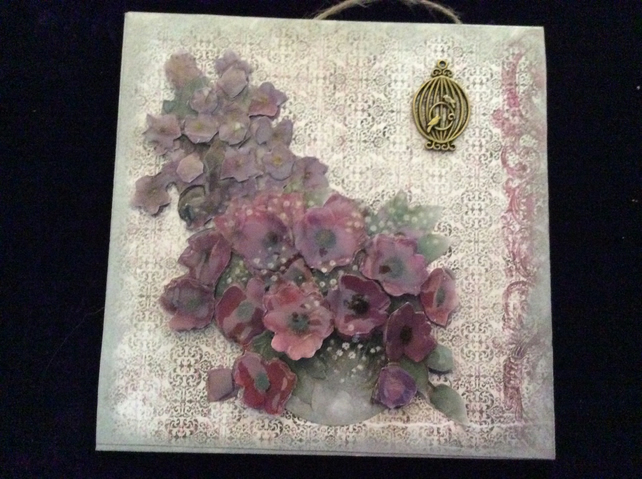 Plaque with bowl of purple flowers.