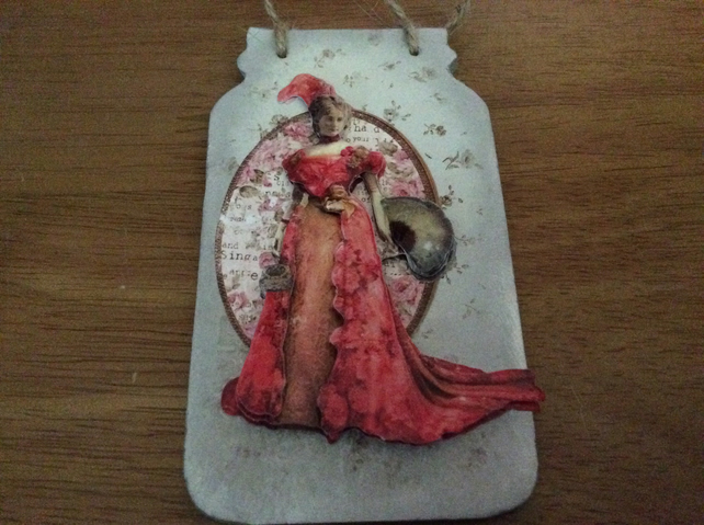 Jar shaped plaque with lady in red.