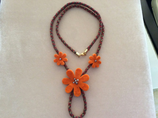 Orange felt flowers on rust and gold cord