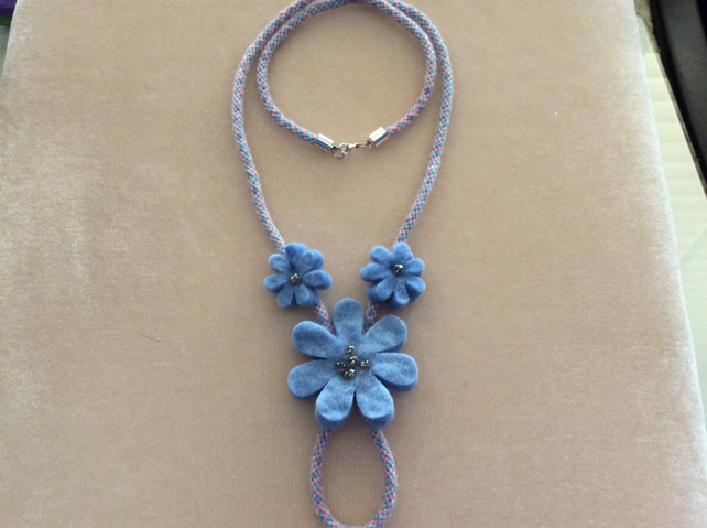 Blue felt flowers on hand worked kumihimo cord necklace.