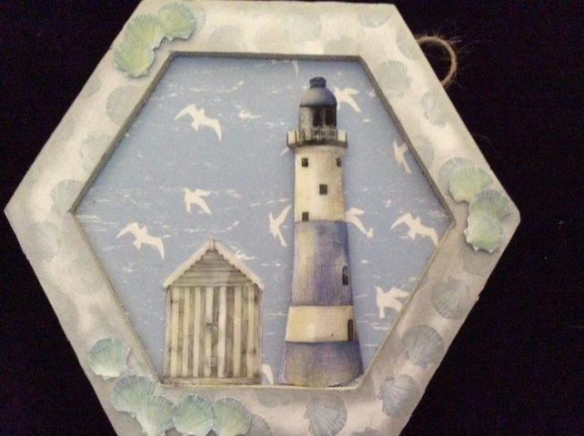 Hexagon lighthouse with beach hut and shells.