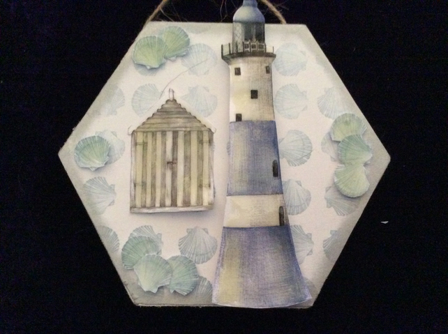 Small hexagon plaque with lighthouse and beach hut.