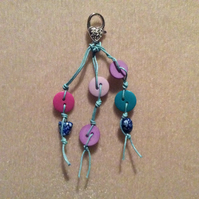 Turquoise Corded Bag Charm With Pink, Purple & Blue Beads And A Silver Clasp.