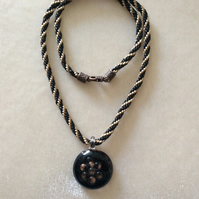 Black & Gold Kumihimo Cord Necklace With A Black & Gold Glass Pendant.